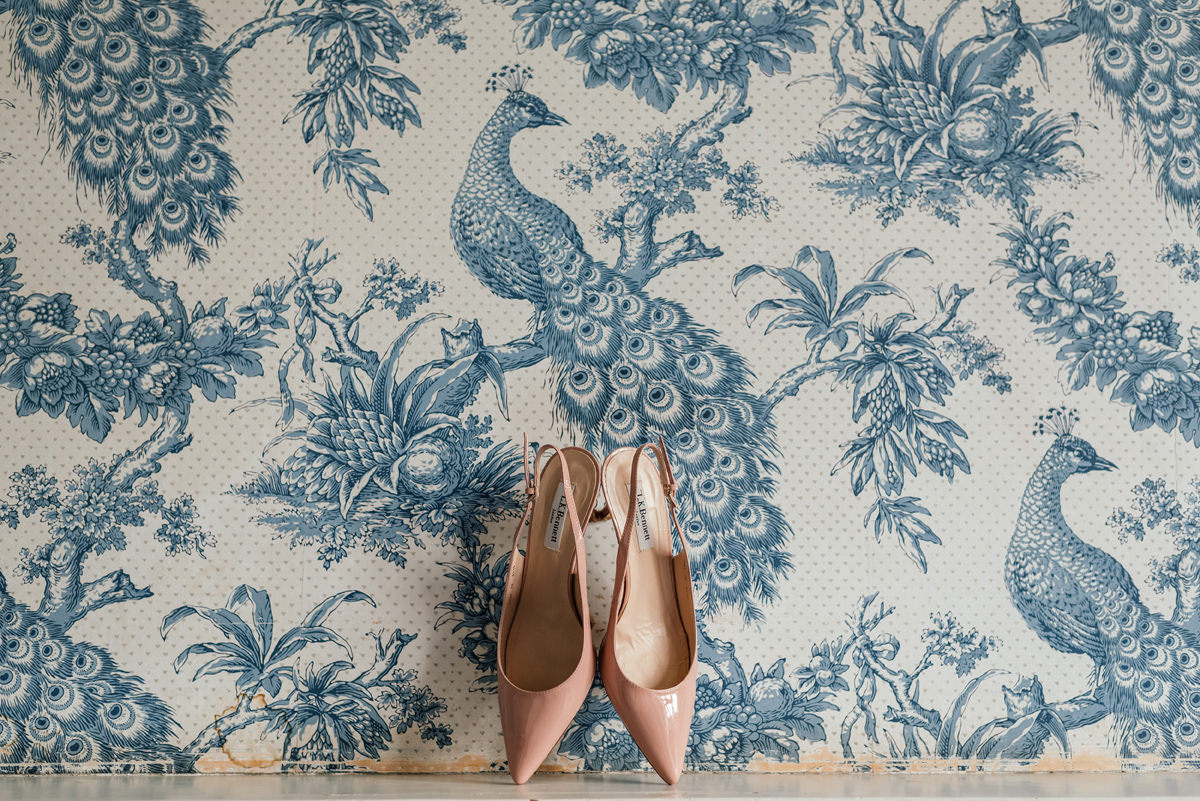 Bride's wedding shoes against fancy wallpaper