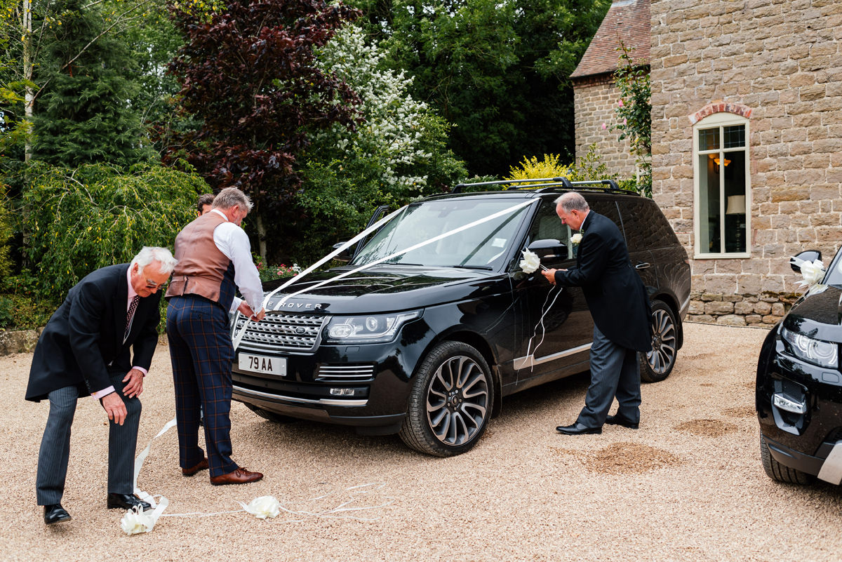father of the bride puts ribbons on the wedding cars