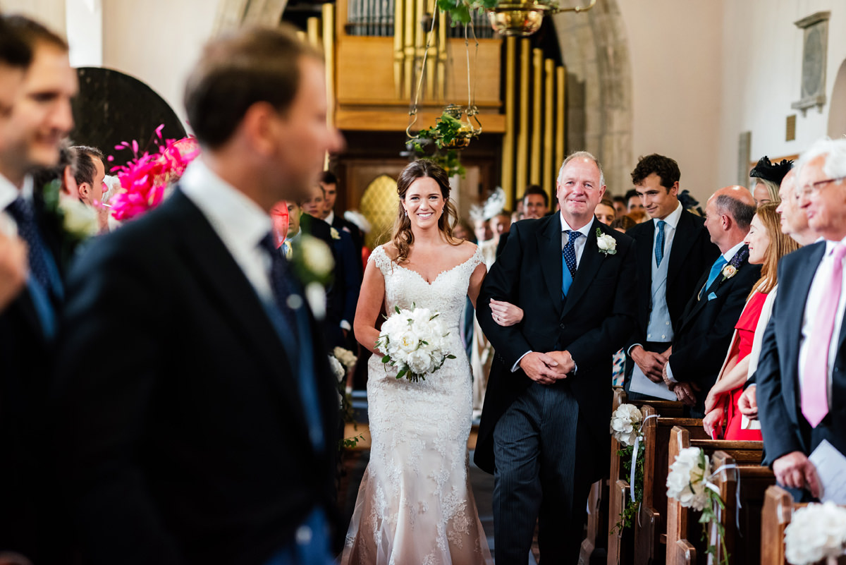 bride and her father walk down the aisle in church
