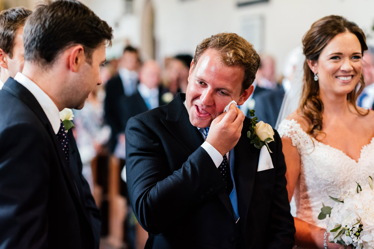 groom wipes away a tear as his bride arrives for the ceremony