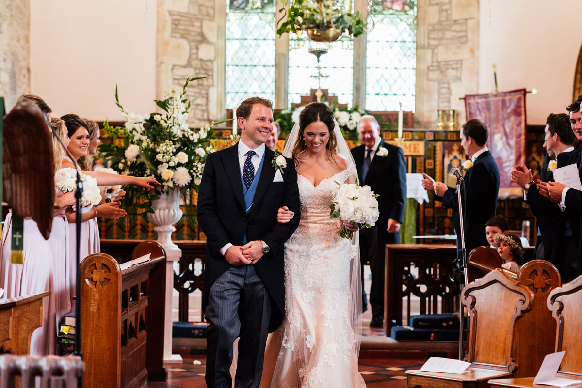 bride and groom leave the church as a married couple