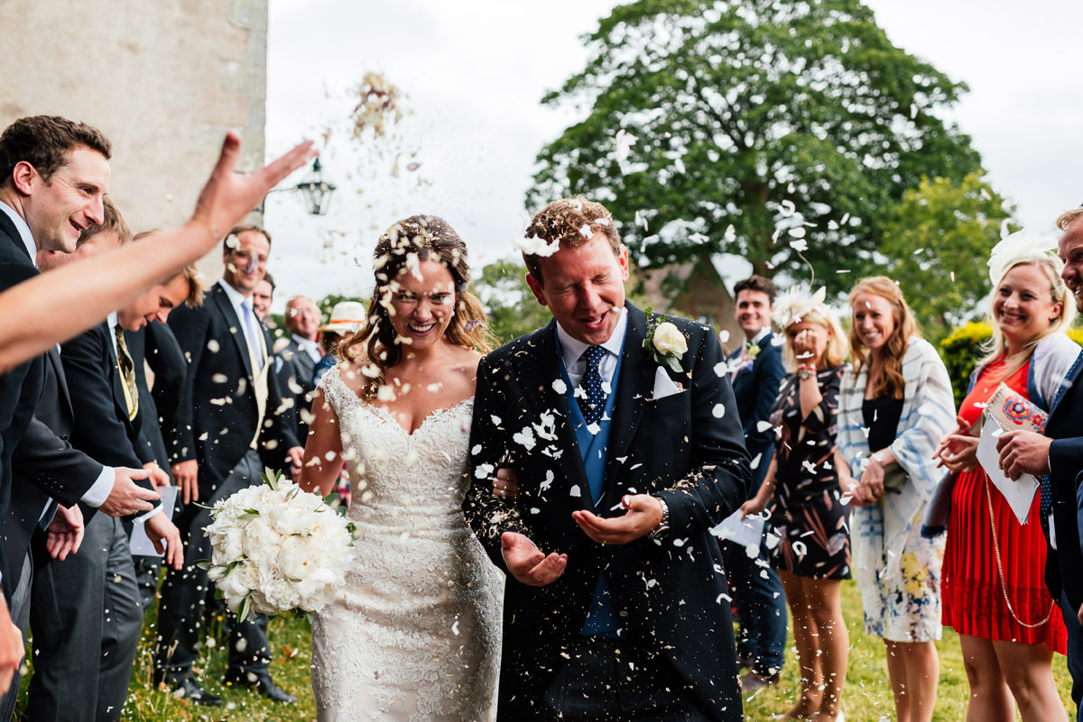 bride and groom get showered in confetti