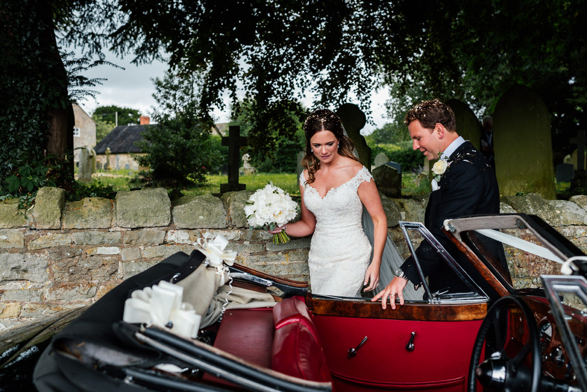 bride and groom get into the wedding car