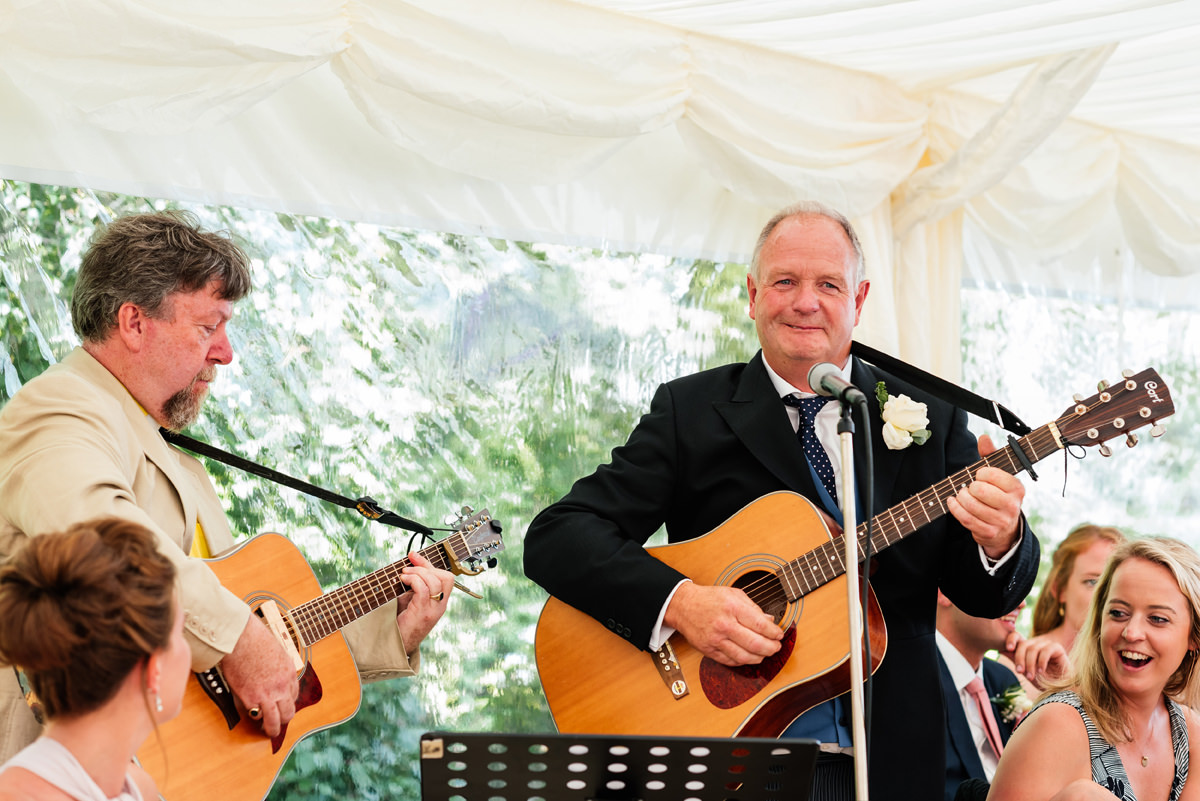father of the bride sings and plays guitar as part of his speech