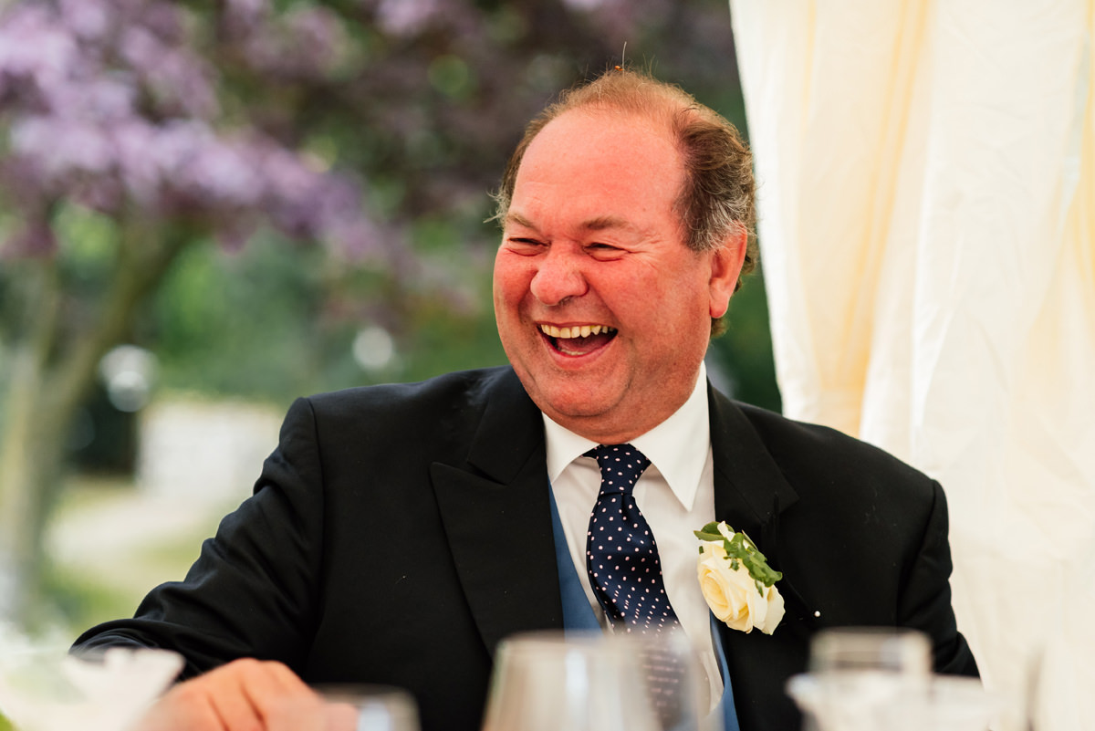 father of the groom laughing during the speeches