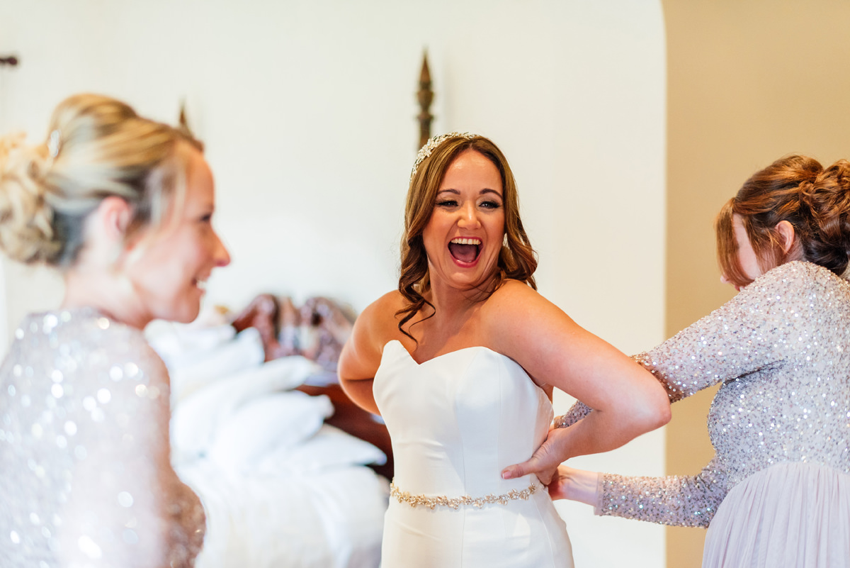 bride smiling while getting in wedding dress