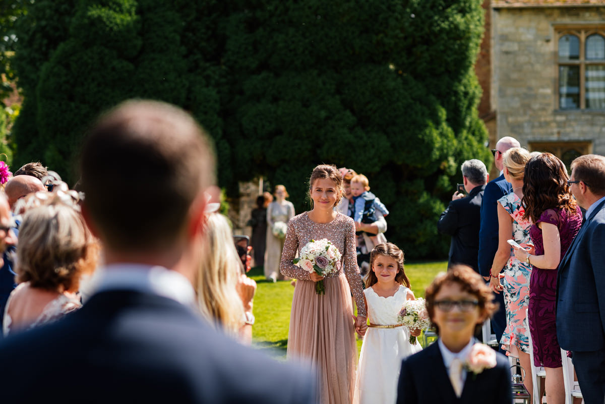 bridesmaids walking down aisle for outside ceremony