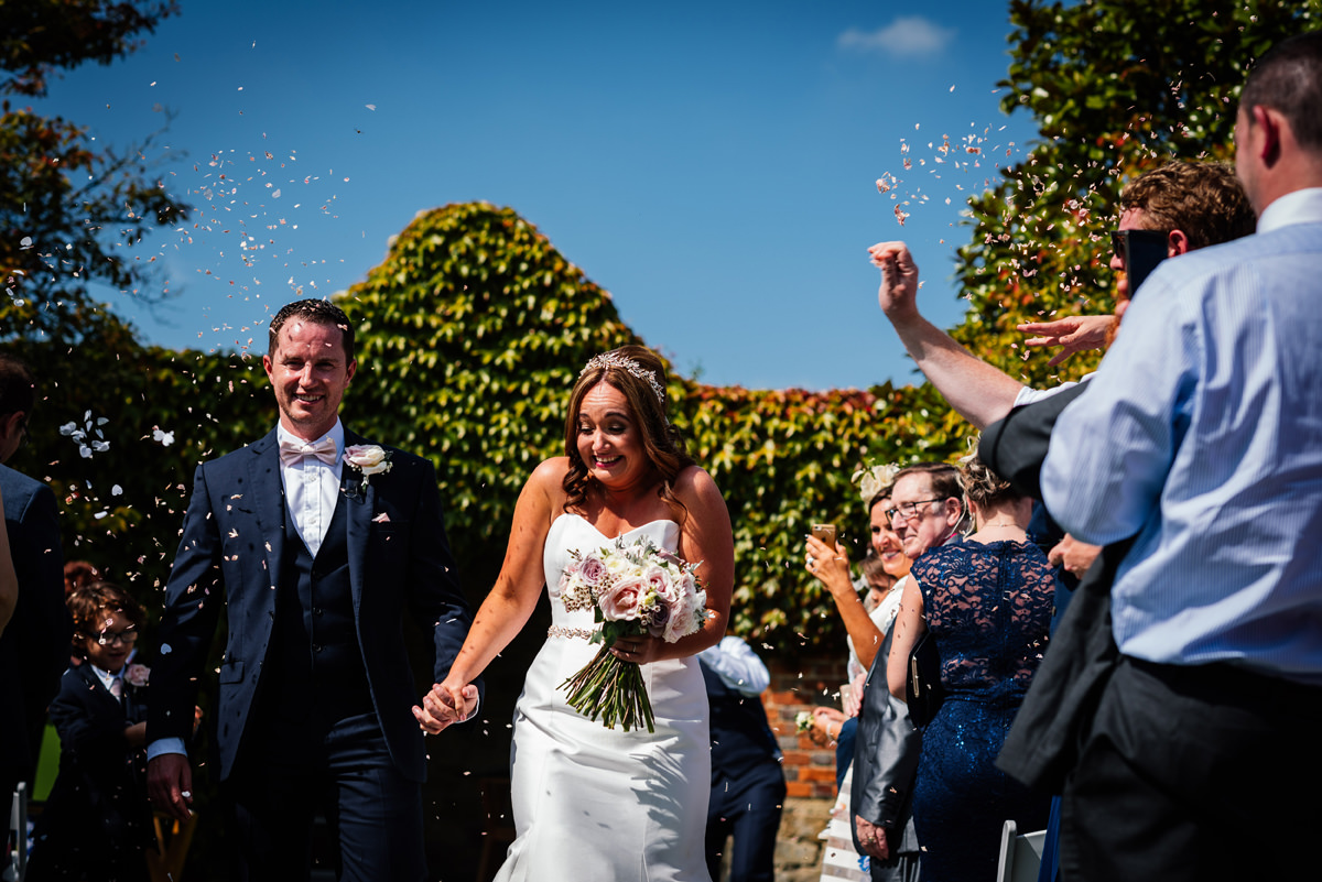confetti being thrown at bride and groom
