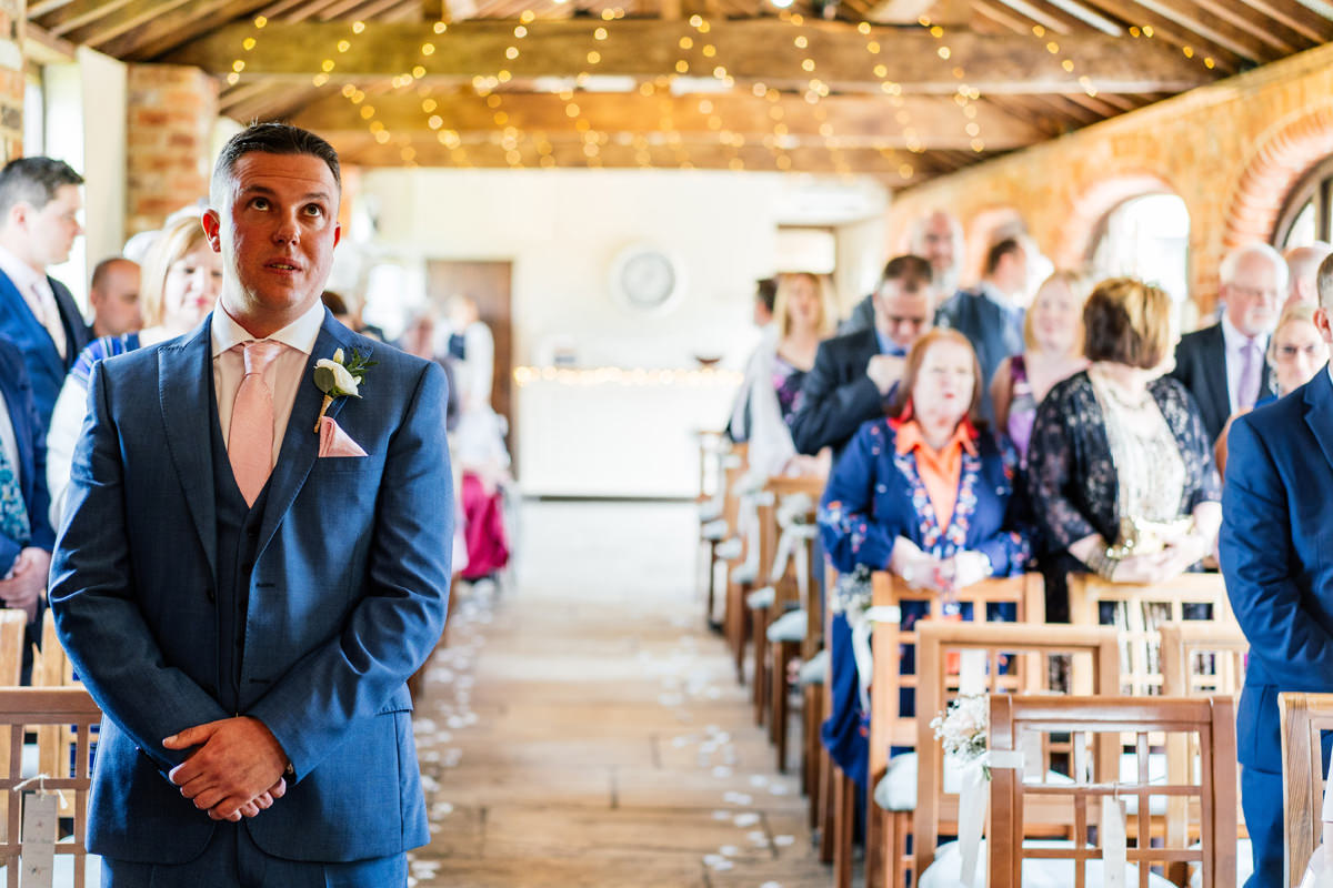 groom waits for bride in ceremony