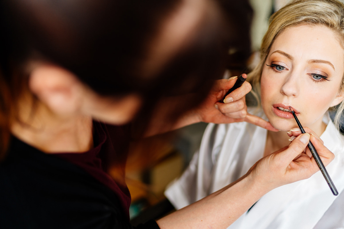 bride having her make-up done on morning of her wedding day
