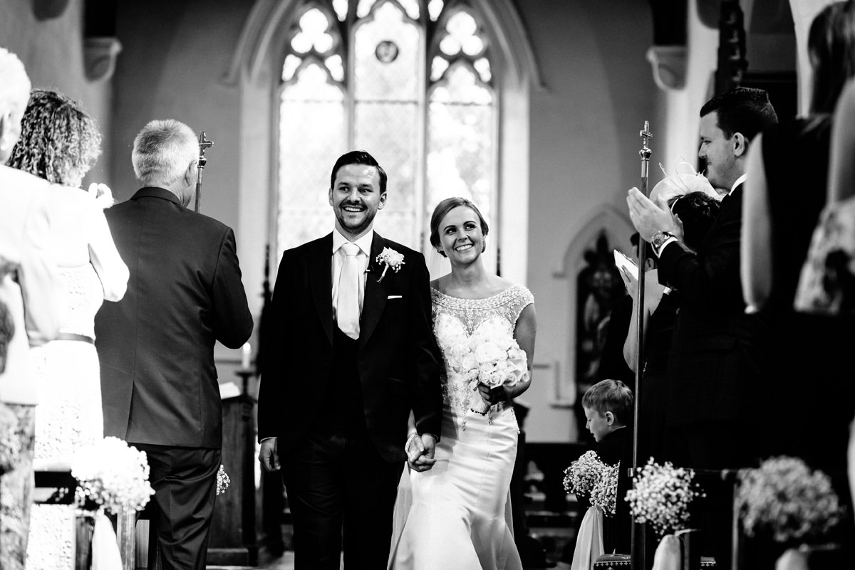 bride and groom leaving the church as a married couple