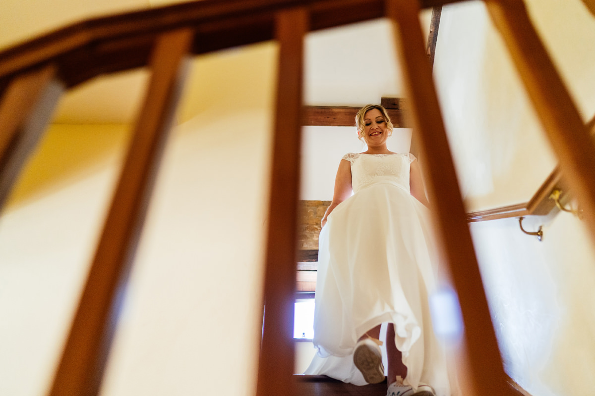 bride walks down stairs in wedding dress