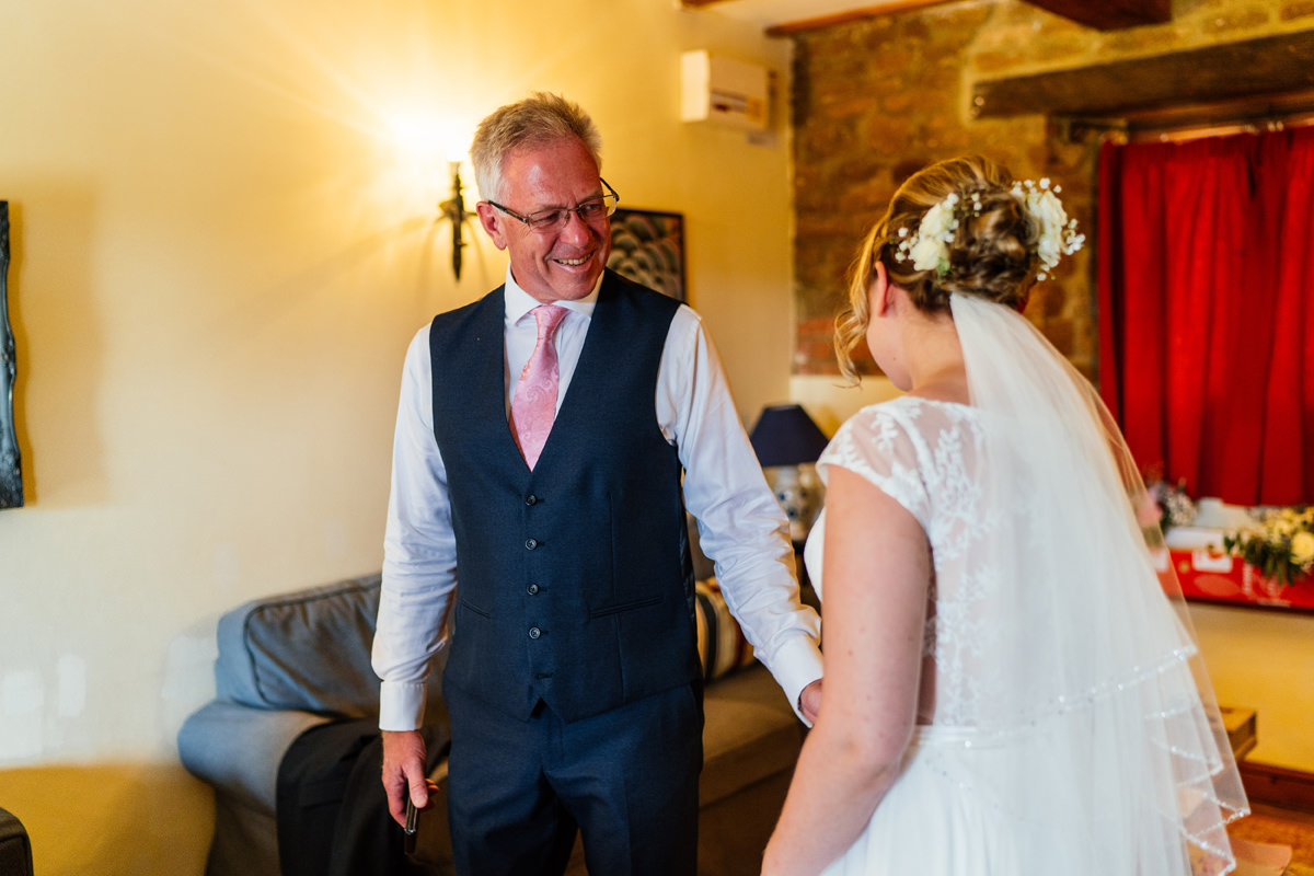 father of bride sees his daughter in her wedding dress for the first time
