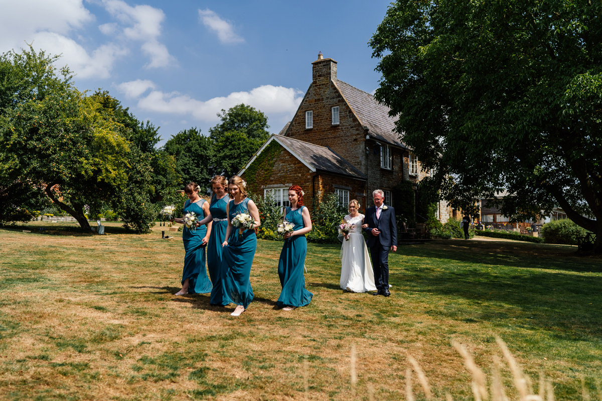 bridesmaids make their way to the outdoor ceremony