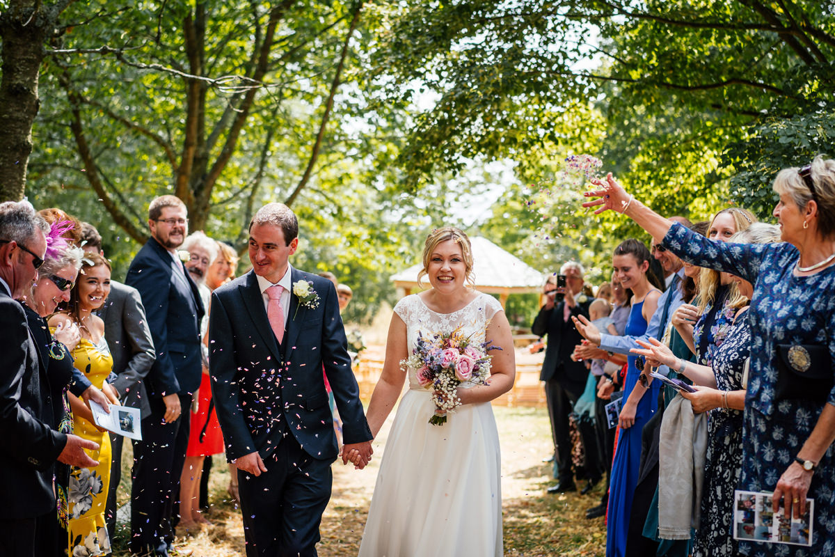 bride and groom leave the ceremony and guests throw confetti.