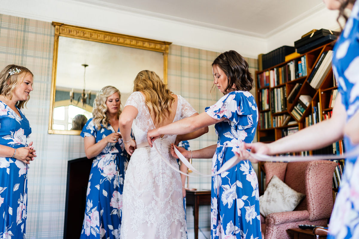 bride getting into her wedding dress helped by her bridesmaids