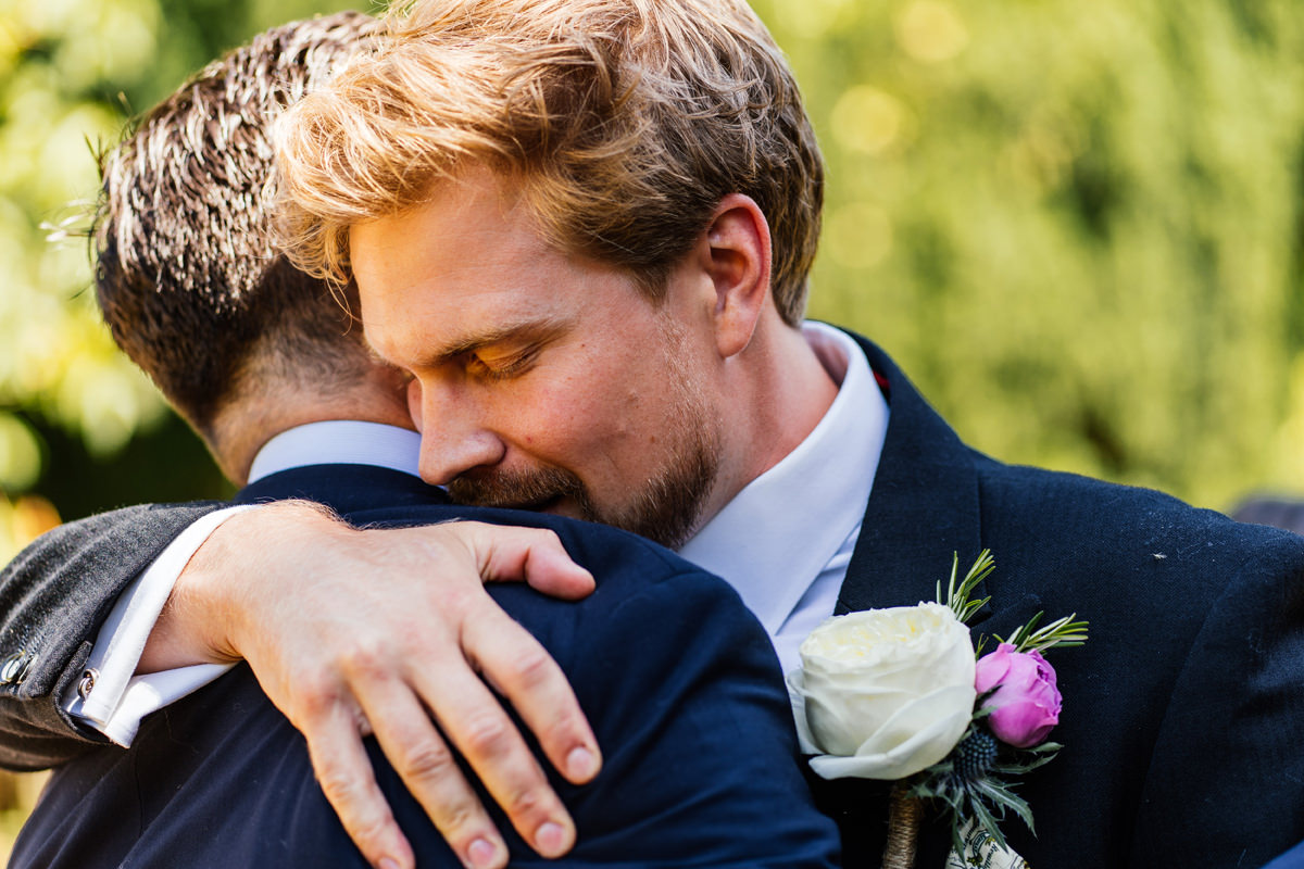 groom hugging a wedding guest at the church