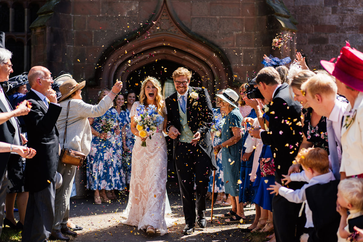 bride and groom are showered with confeetti