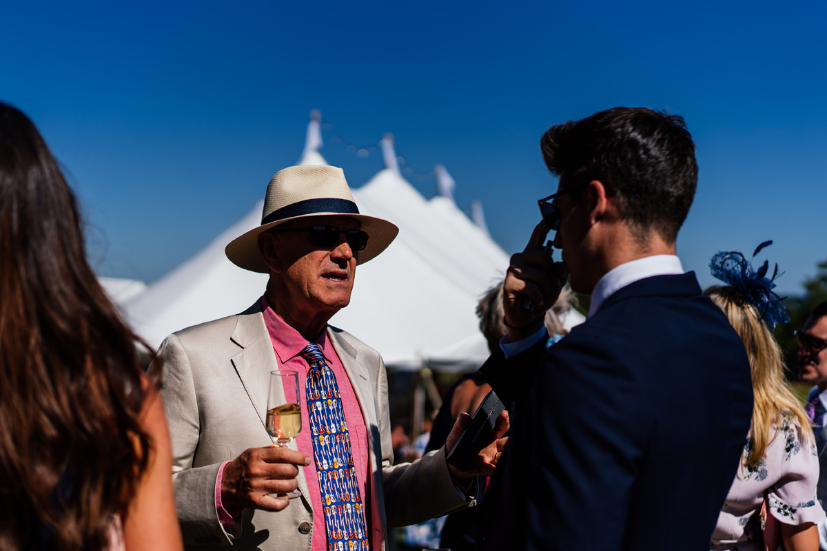 gentleman wearing a hat with the wedding marquee in the background