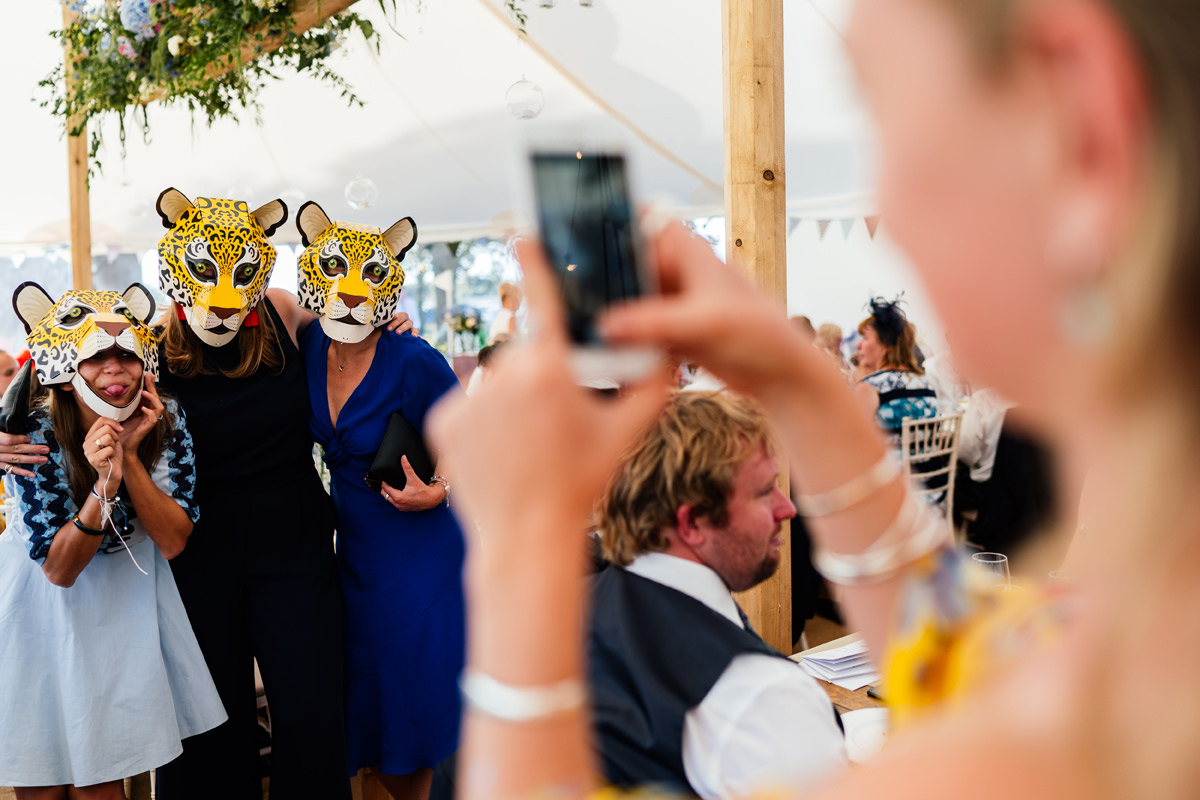 wedding guests having their photo taken whilst wearing fun animal masks
