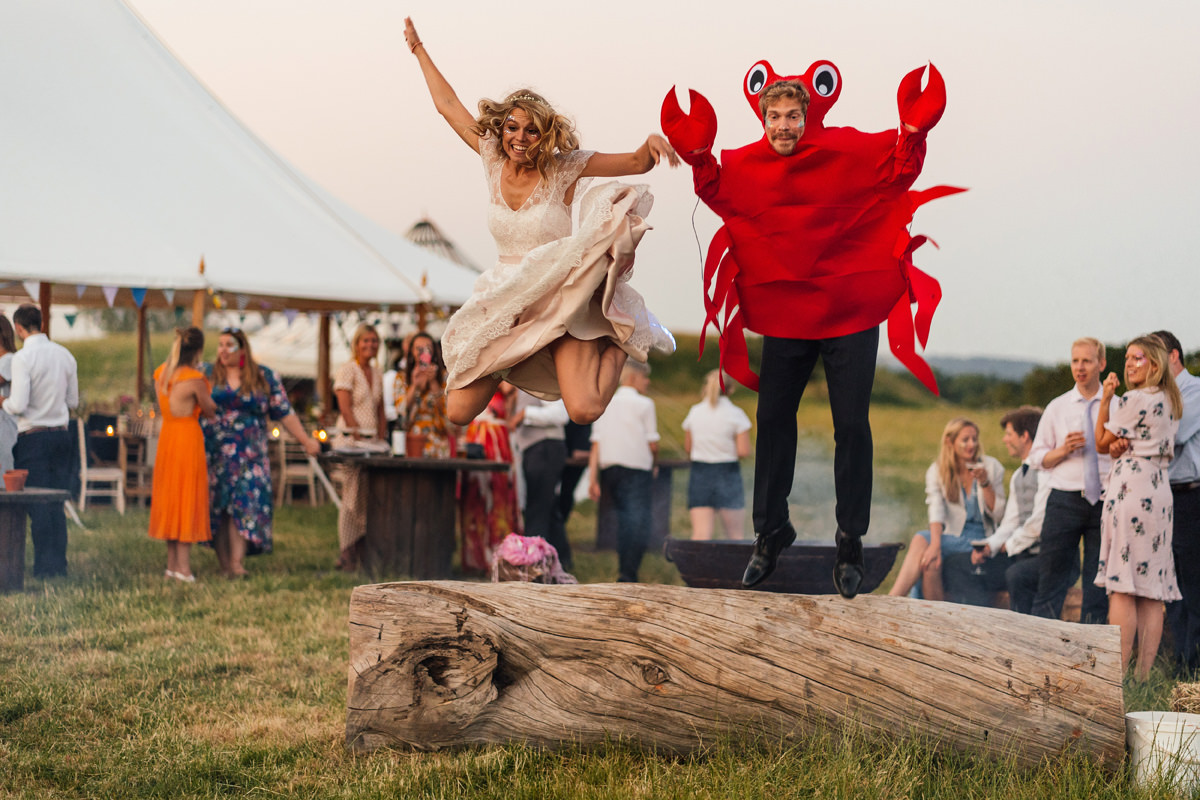 final photo of the wedding bride and groom jumping off a log groom dressed as a lobster