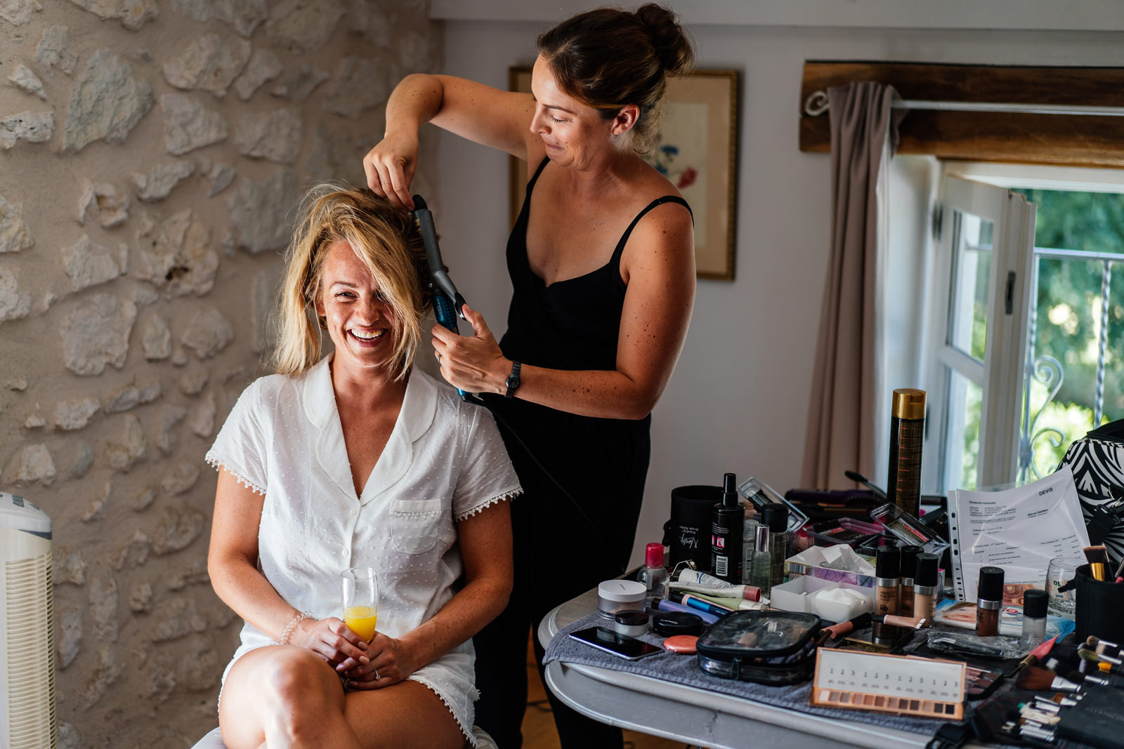 bride having her hair done in the morning of wedding