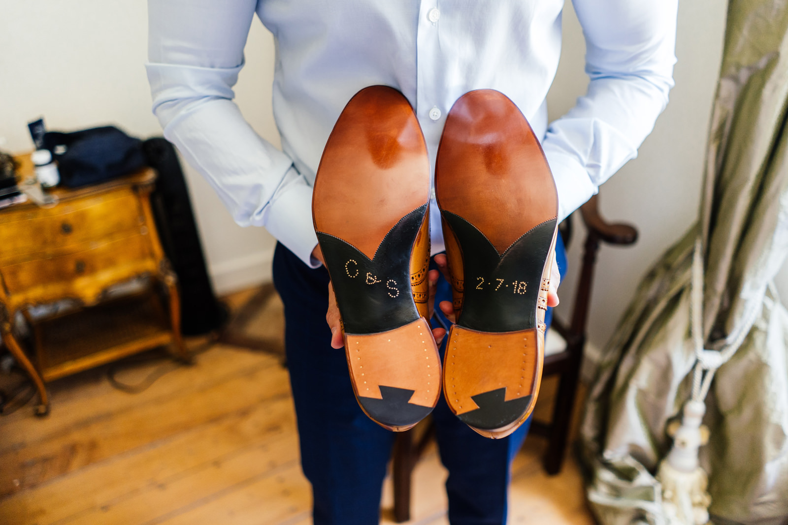 groom holding his wedding shoes