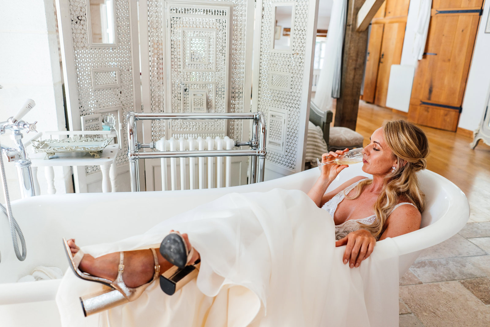 bride in her wedding dress drinking champagne in the bath