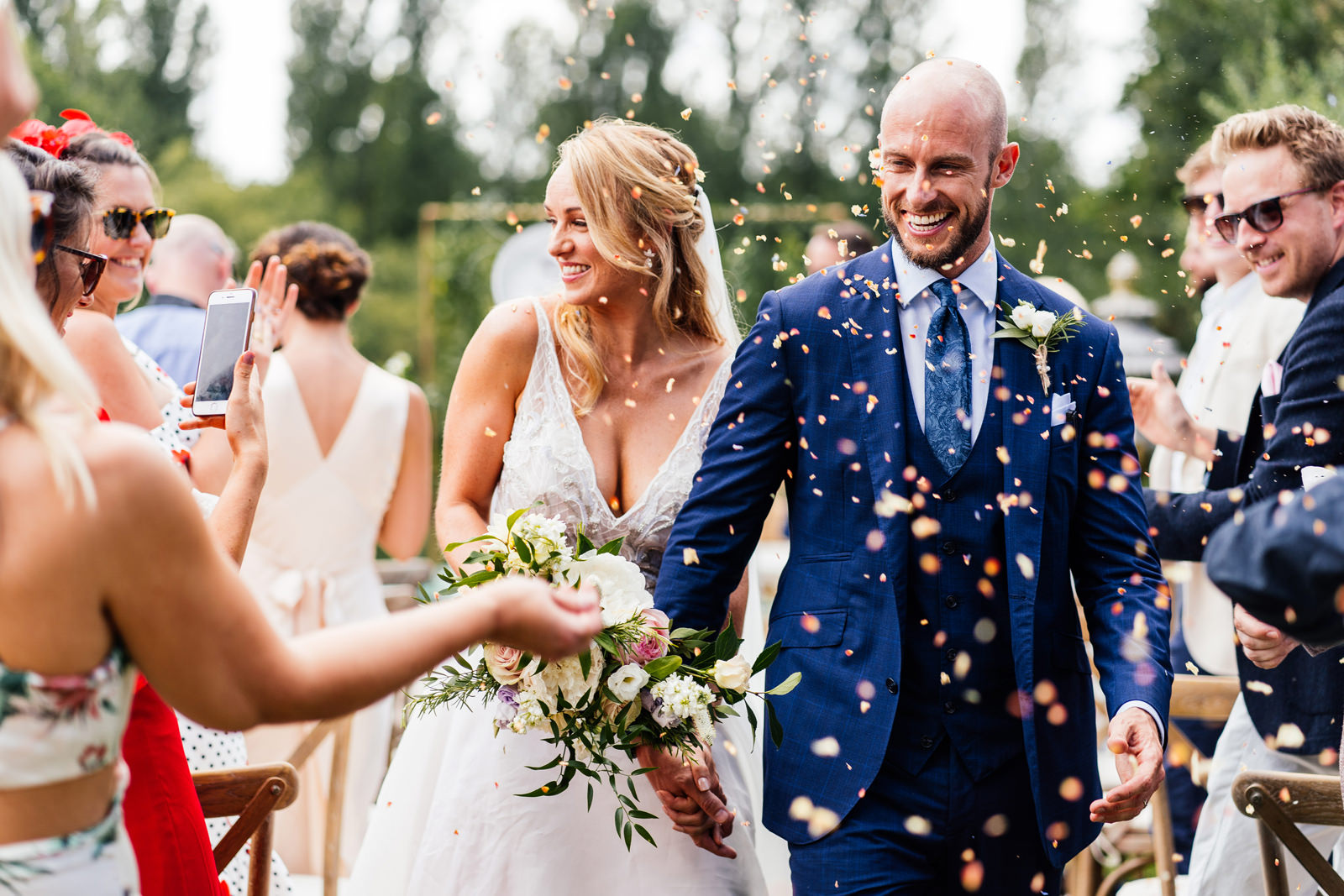 bride and groom showered with confetti at the end of the outdoor ceremony