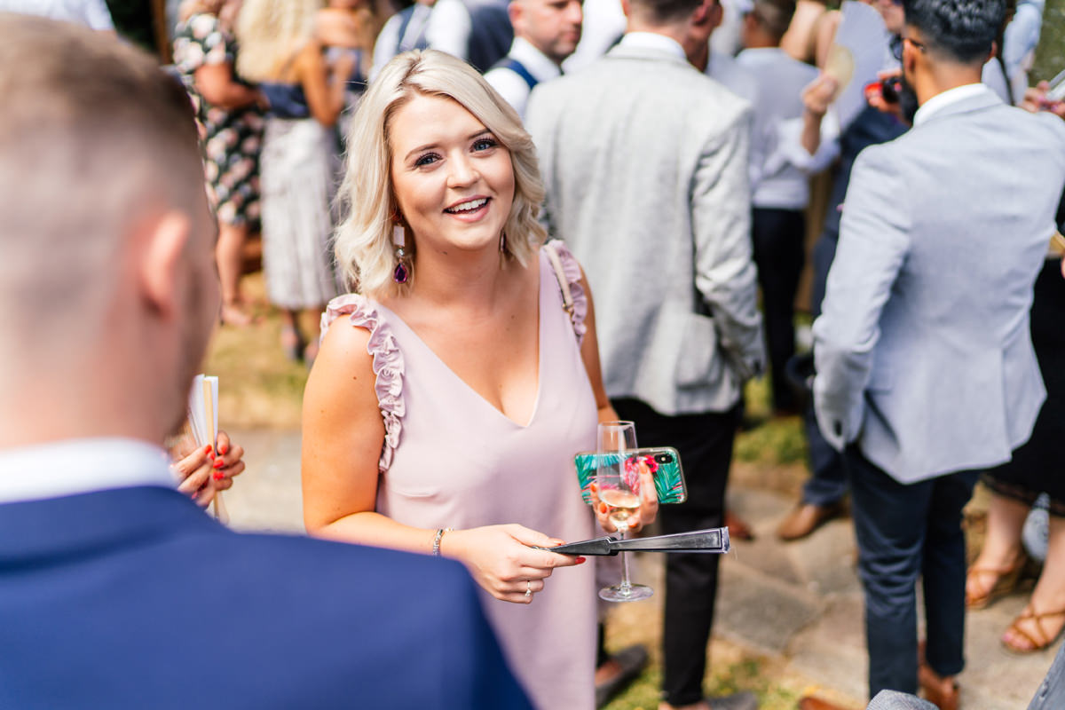 wedding guest smiling during drinks reception