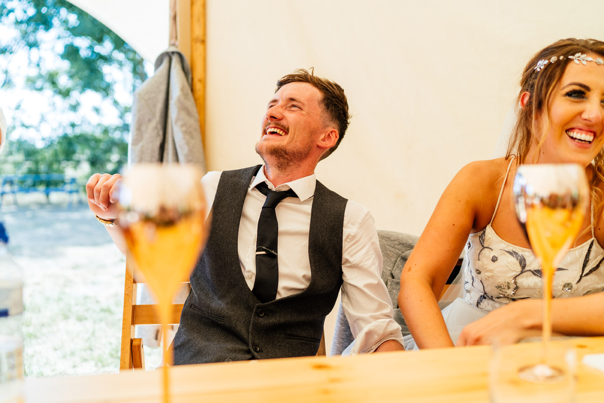 groom and bride laughing during best man speech