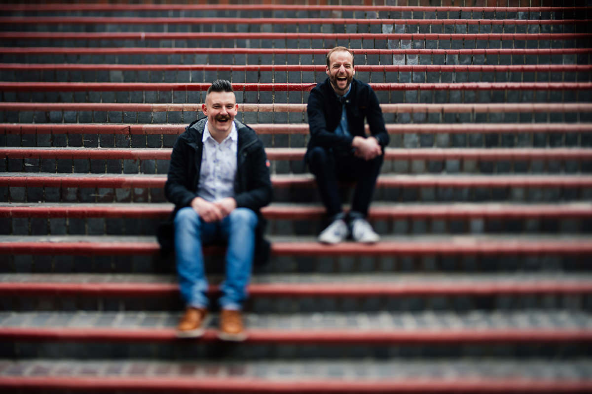 sitting on the steps of the barbican gay pre-wedding shoot
