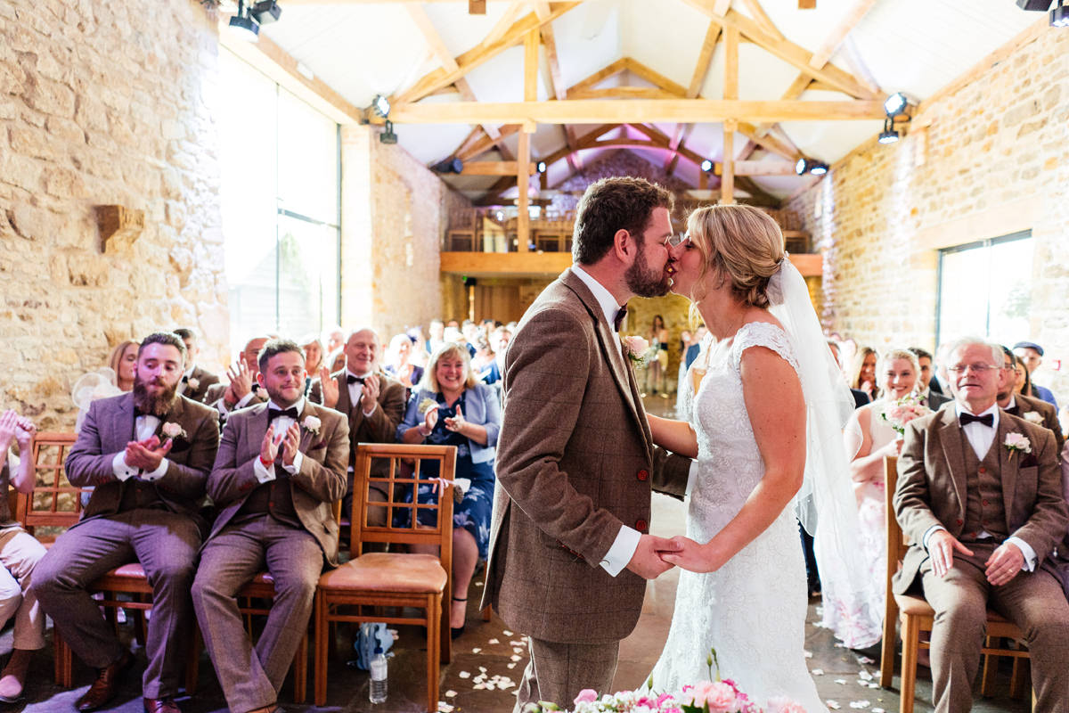 the bride and groom have their first kiss as a married couple