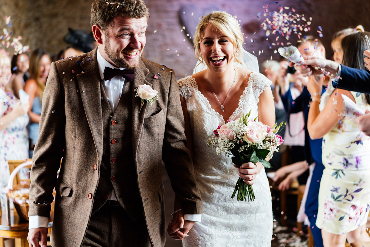 bride and groom exit ceremony with confetti thrown at them