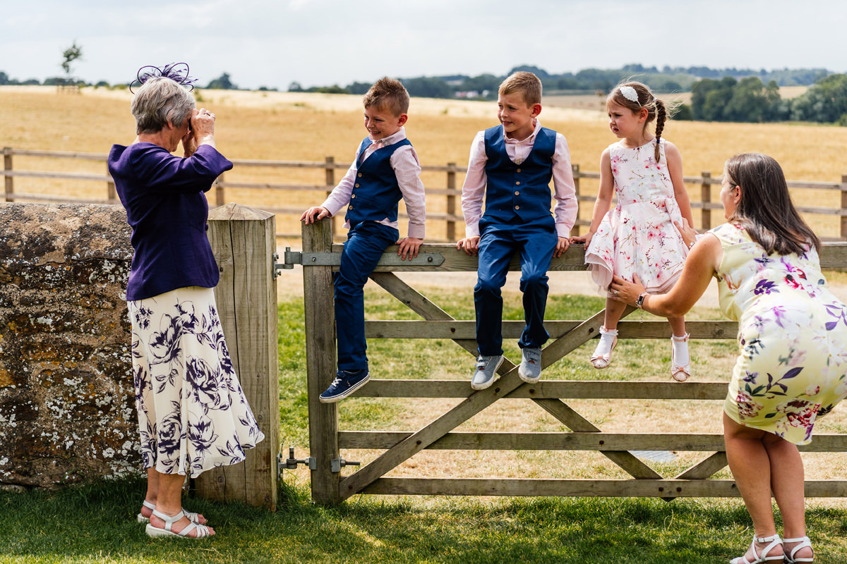 family member takes photos of the young children at the wedding