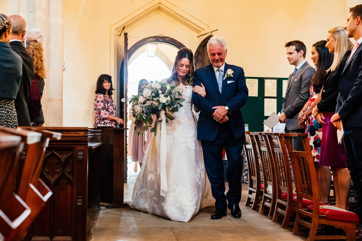 bride enters the church with her father