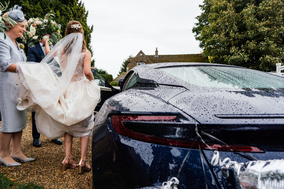 bride leaves the church in aston martin