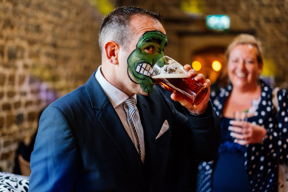 face painted man drinking beer
