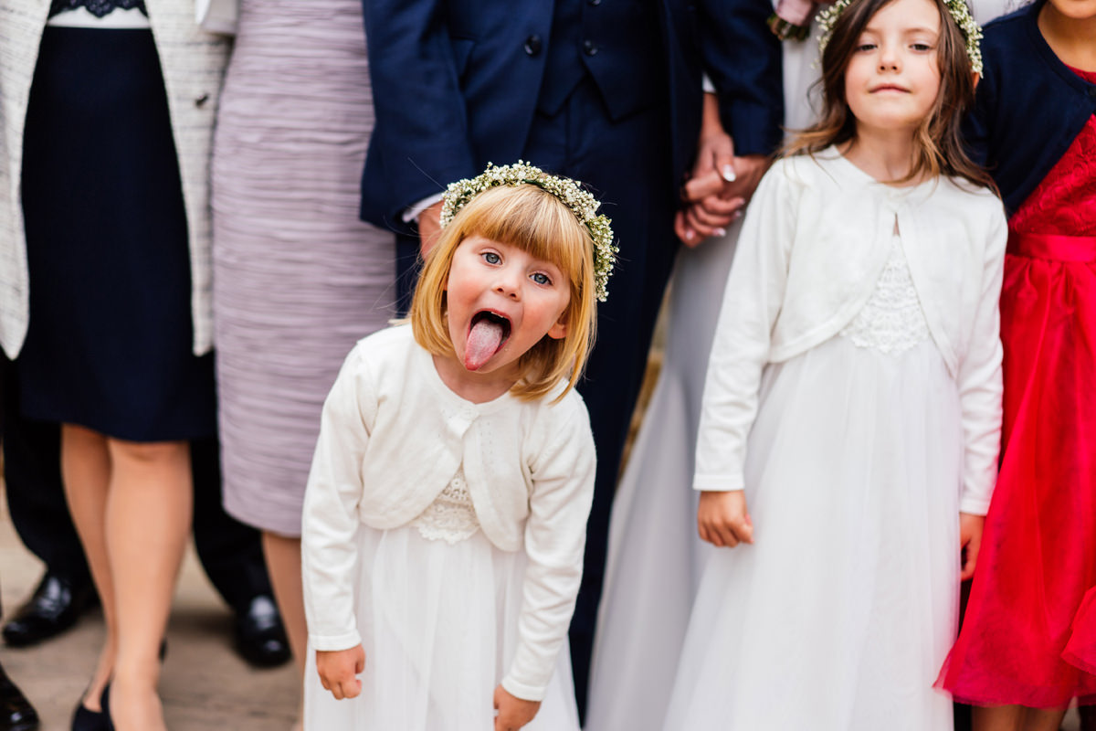 cheeky flower girl sticking her tongue out