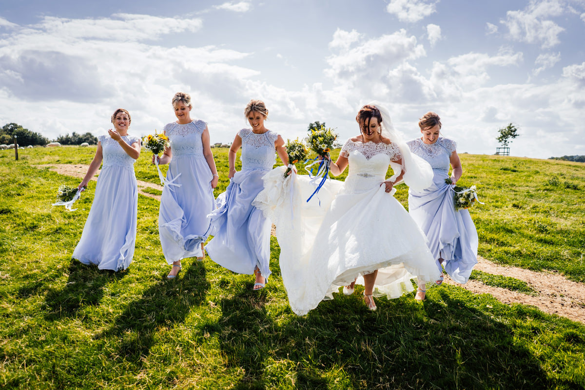 bride and her bridesmaids walking through the field