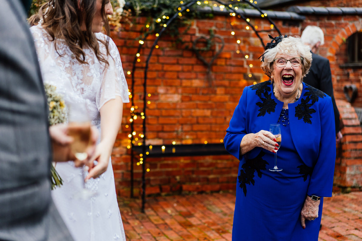 Gran having a drink and a laugh at the wedding