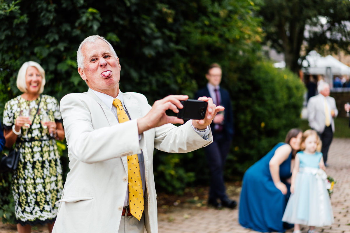 wedding guest sticking his tongue out at me