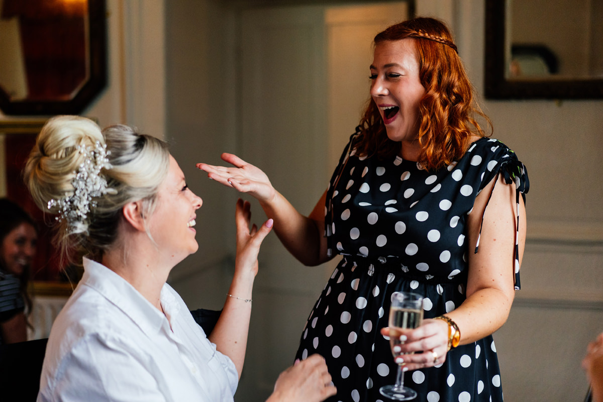 bride and friend laughing during bridal prep