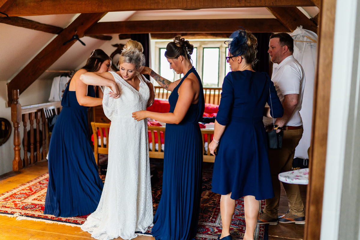 bride gets into her wedding dress helped by her bridesmaids