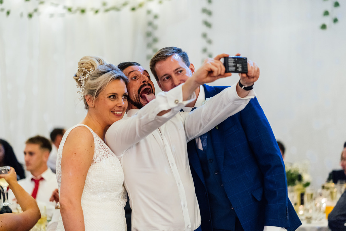 wedding guest takes a selfie with the bride and groom