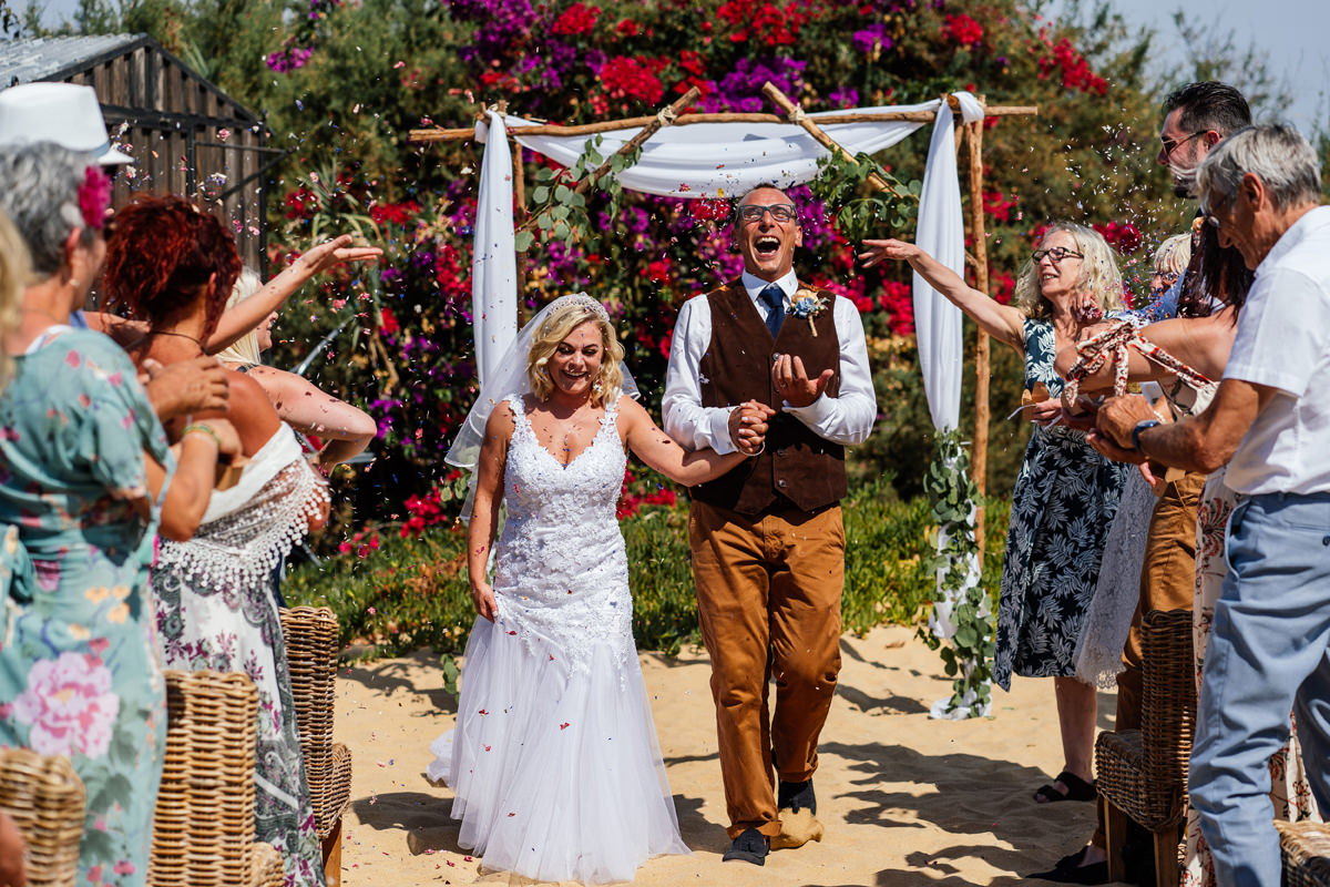 bride and groom walk down the beech aisle with guests throwing confetti