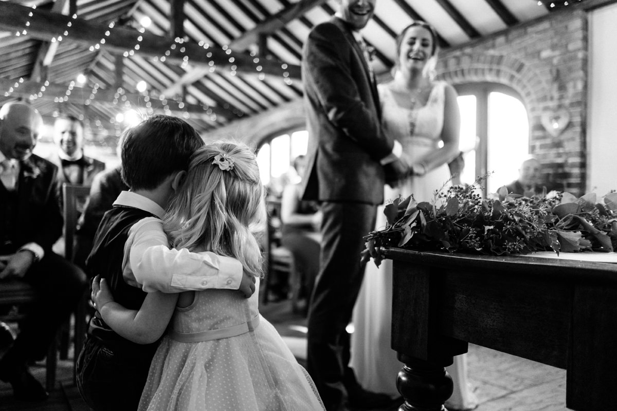 flower girl and page boy have a hug during the ceremony