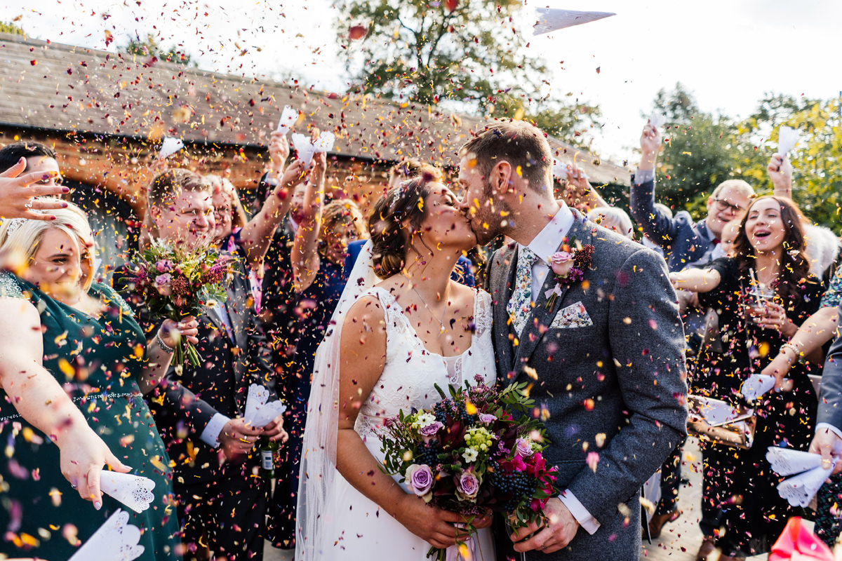bride and groom kiss while being showered with confetti