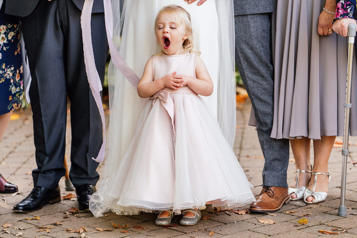 Flower girl yawning during the group photos
