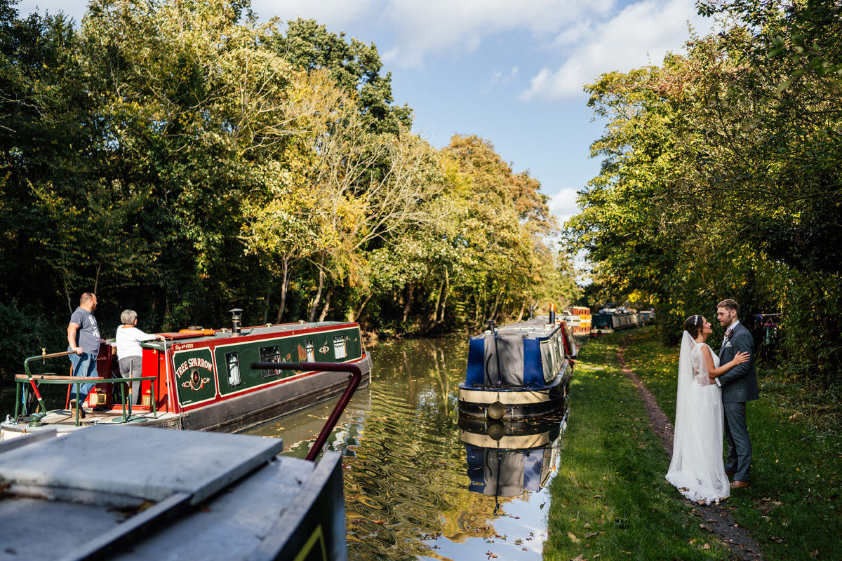 canal boats pass the bride and groom during portraits